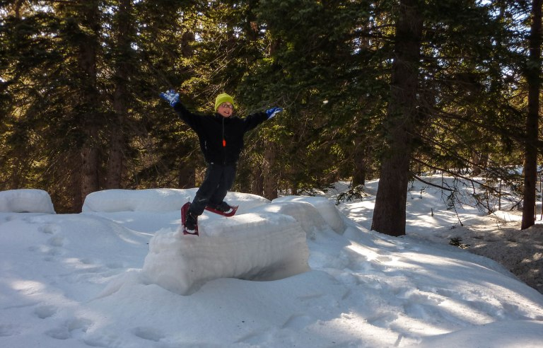 Snowshoeing in American Fork Canyon; he's jumping off a snow covered bench in a campground.